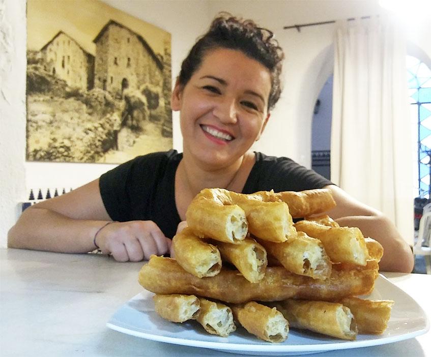 Conchi, una de las churreras, con un plato con varias raciones de churros del Mesón Castellano Casa Soria. Foto: Cosasdecome