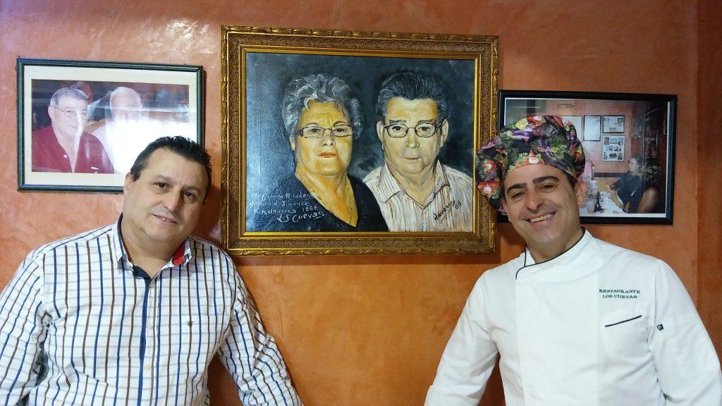 Los hermanos José Manuel y Joaquín León Roldán, junto a una pintura en la que aparecen sus padres y que está colgada en el comedor del restaurante. Mari Carmen fue primera que realizó el plato. Foto: Cosasdecome.
