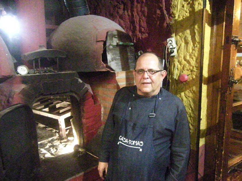 Tomás Laúl junto al horno en el que asan cochinillos y corderos. Foto: Cosasdecome