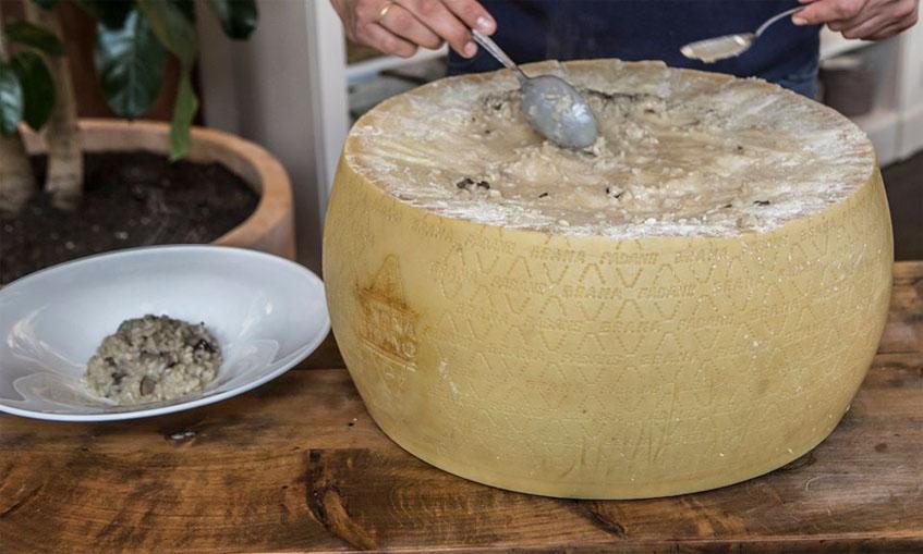El risotto se termina de preparar en el comedor y dentro de un gigantesco queso. Foto: Cedida por el grupo La Raza.
