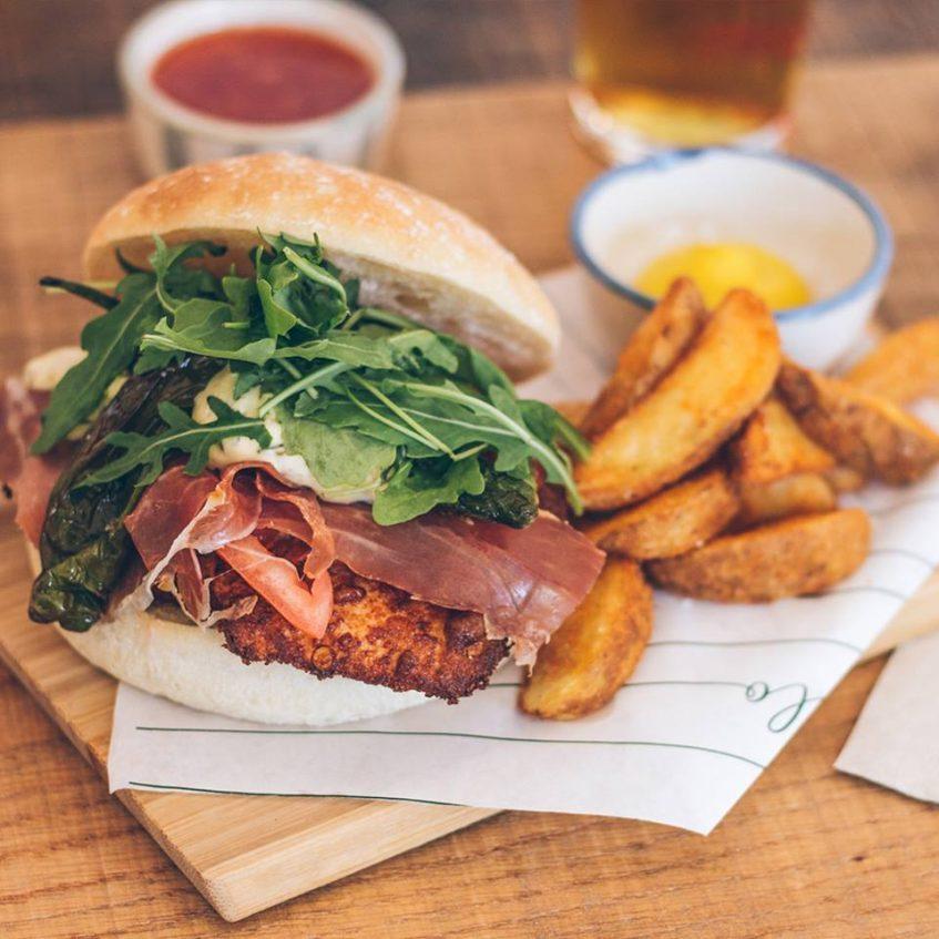 Burger Chikenito, con pollo frito con panko, tomate, jamón serrano, padrones fritos, rúcula y salsa tártara. Foto cedida por establecimiento
