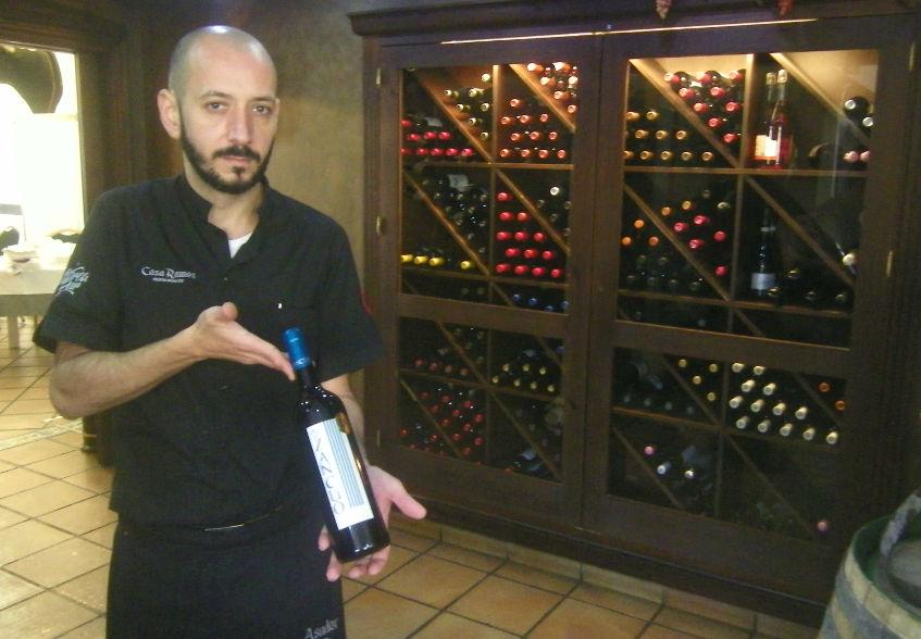 Uno de los camareros de Casa Ramos posa junto a la bodega del establecimiento con una botella de Zancúo, el vino de las bodega Las Margaritas de Constantina. Foto: Cosasdecome