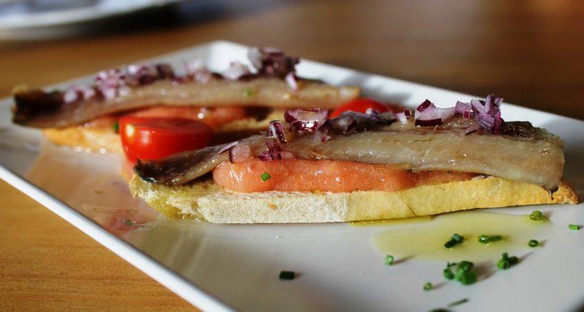 Crostini de sardina ahumada sobre pomada de tomate. Foto: Cosas de Comé