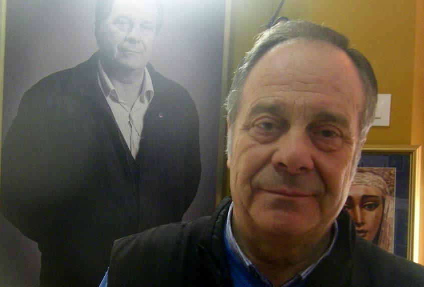 Manolo Santos delante de un retrato suyo que está expuesto en el bar. Foto: Cosasdecome