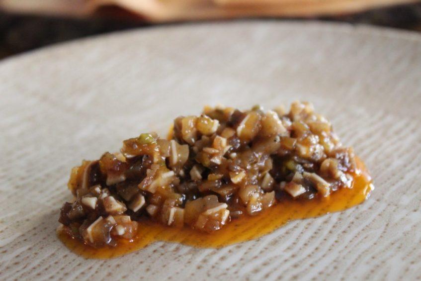Tartar de oreja, raíces de mostaza fermentadas y emulsión de aove, ajo tostado y soja. Foto: Cosas de Comé