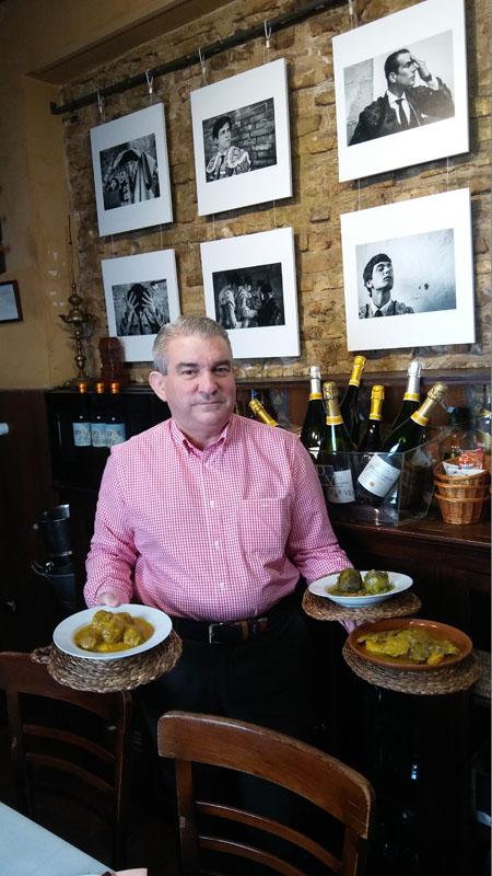 Ramón López de Tejada, el gerente de la antigua abacaría con varios de los platos de las jornadas. De fondo una exposición de fotos de toreros que se expone también en estos días en el establecimiento. Foto: Cosasdecome