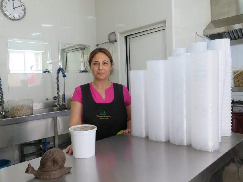 Paqui Lora ante las tarrinas de caracoles que le han dado fama más allá de Sevilla Este. Foto: CosasDeComé.
