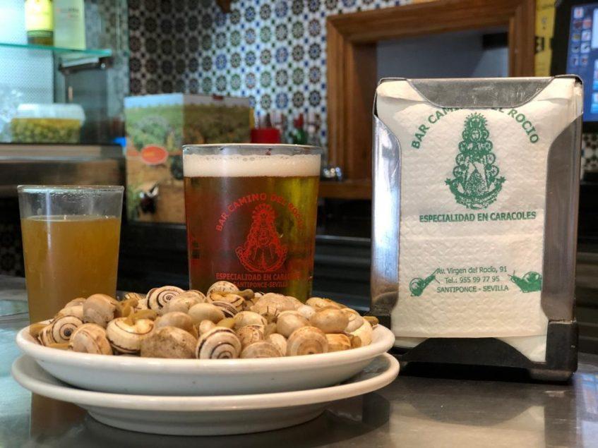 Cerveza y vaso de caldo, complementos casi indispensables de los caracoles del Bar Camino del Rocío. Foto: CosasDeComé.