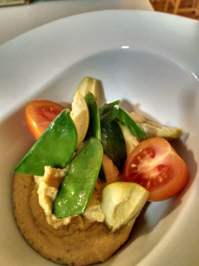 Hummus de garbanzos con cebollino picado terminado con tomate cherry, tirabeque y aceituna verdes. Foto cedida por el establecimiento.