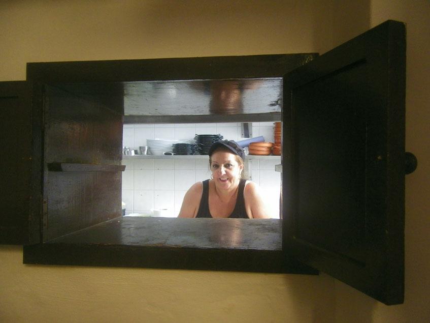 La cocinera Loli Calero es la que elabora actualmente las pavias. En la foto aparece en un ventanal por el que salen los platos directamente desde la cocina a uno de los comedores del establecimiento. Foto: Cosasdecome
