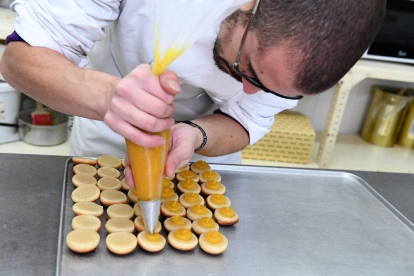 Colocación de la crema de batata que une las dos mitades del dulce para que terminen en un beso. Foto cedida por el establecimiento.