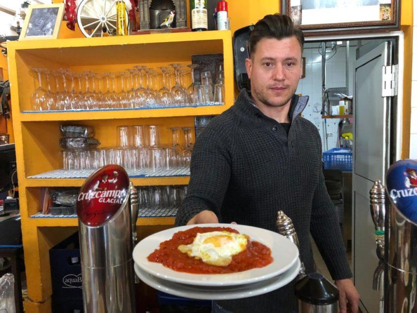 Relu Andrei, de Casa Batato, muestra el tomate frito con huevos y patatas fritas, especialidad de la casa. Foto: CosasDeComé