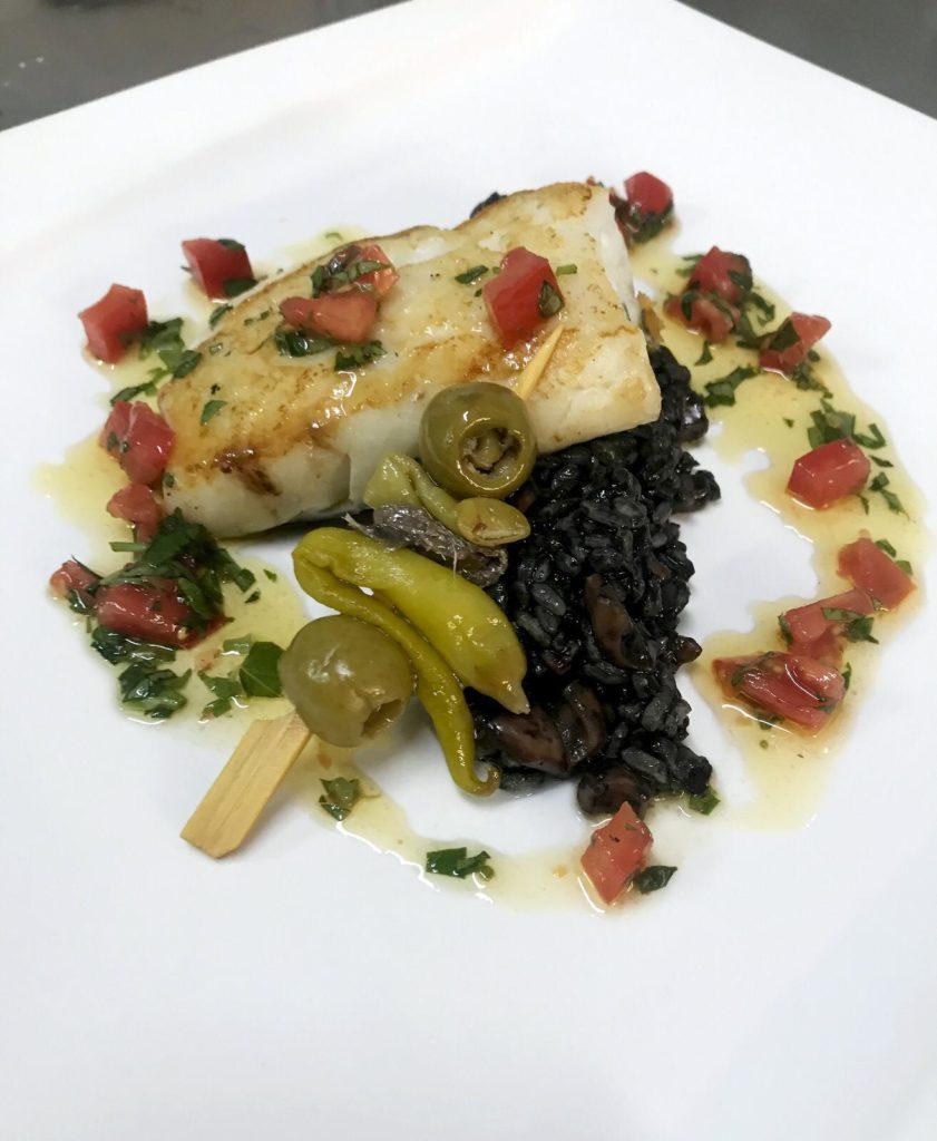Bacalao confitado sobre arroz negro cremoso y un aceite de albahaca. Foto cedida por el establecimiento