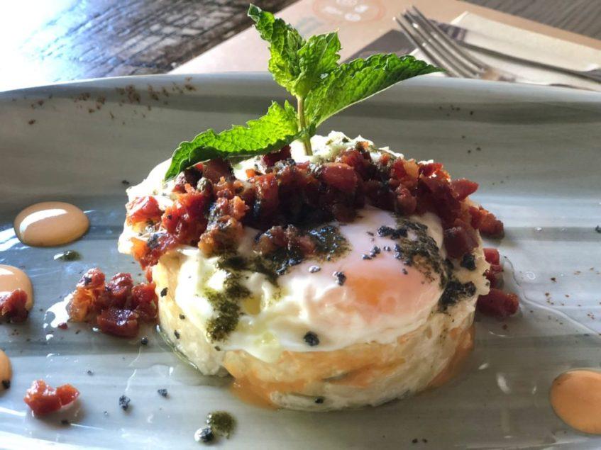 Esta innovadora ensaladilla se culmina con jamón, un huevo frito y una hoja de laurel. Foto: CosasDeComé